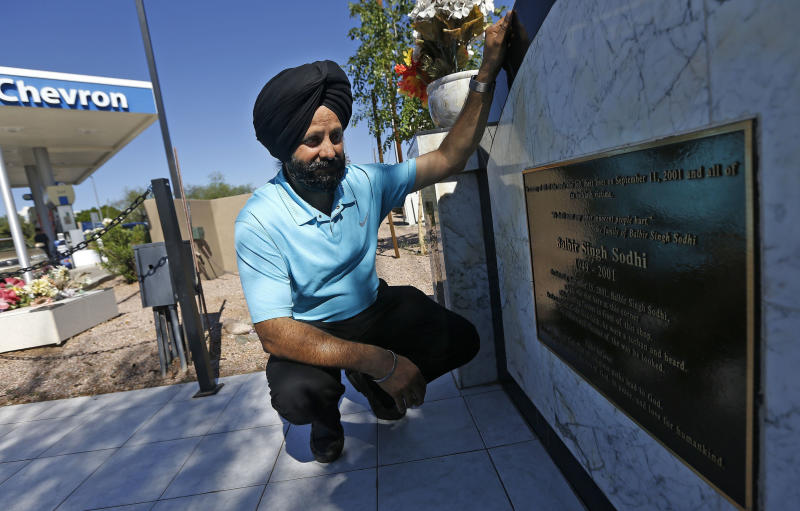 FILE - In this Aug. 19, 2016, file photo, Indian Sikh immigrant Rana Singh Sodhi kneels next to a memorial in Mesa, Ariz., for his murdered brother, Balbir Singh Sodhi, who was gunned down at the site four days after the Sept. 11, 2001 attacks by a man who mistook him for a Muslim because of his turban and beard. Sodhi has preached a message of peace and tolerance in hopes of helping others better understand his religion, the fifth largest in the world with some 25 million adherents including a half-million in the United States. (AP Photo/Ross D. Franklin, File)