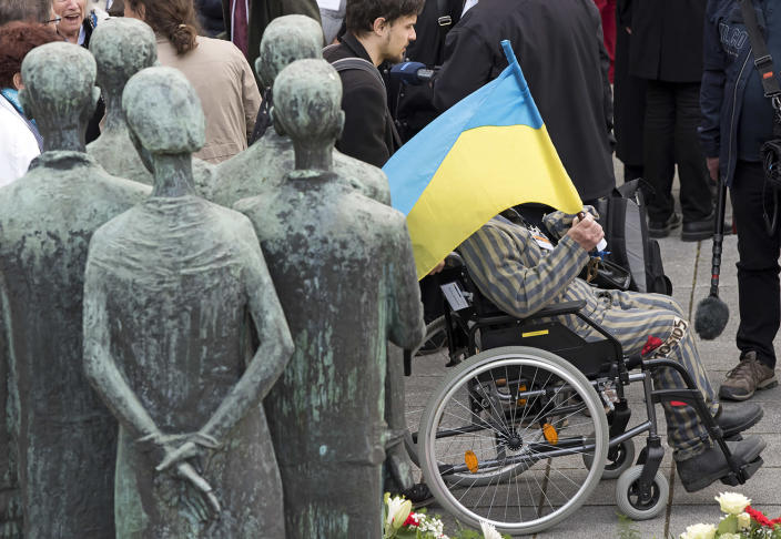 <p>Nazi concentration camp survivor Petro Fedorowitsch Mischuk of Ukraine holds the Ukrainian flag beside the memorial during the commemoration ceremonies for the 72th anniversary of the liberation of former Nazi concentration camp Mittelbau-Dora near Nordhausen, central Germany, Monday, April 10, 2017. (Photo: Jens Meyer/AP) </p>