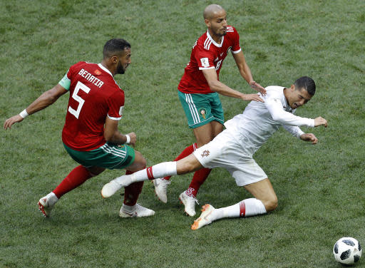 Morocco's Mehdi Benatia, left, and Morocco's Karim El Ahmadi, center, challenge for the ball with Portugal's Cristiano Ronaldo, right, during the group B match between Portugal and Morocco at the 2018 soccer World Cup in the Luzhniki Stadium in Moscow, Russia, Wednesday, June 20, 2018. (AP Photo/Victor Caivano)