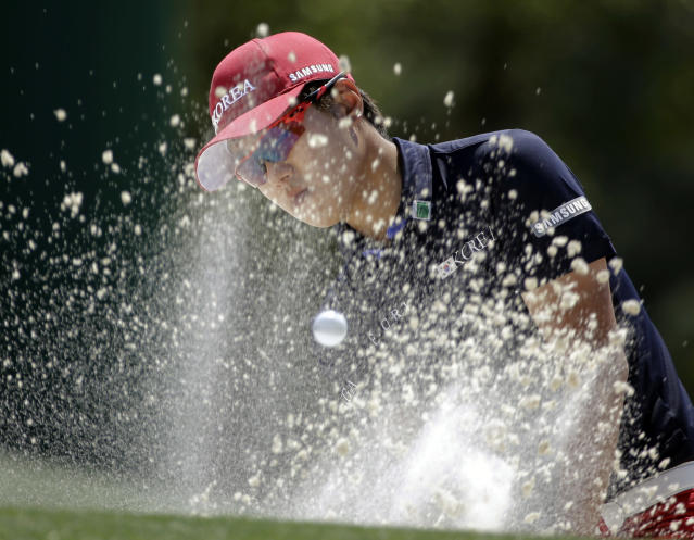 Chang-woo Lee, of Korea hits out of a bunker on the 18th hole during the first round of the Masters golf tournament Thursday, April 10, 2014, in Augusta, Ga. (AP Photo/David J. Phillip)