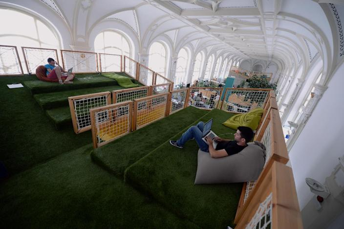 Young employees lounge on beanbags as they work on their lapotops at the headquarters of Hungarian start-up Prezi in Budapest on August 26, 2014 (AFP Photo/Attila Kisbendek)