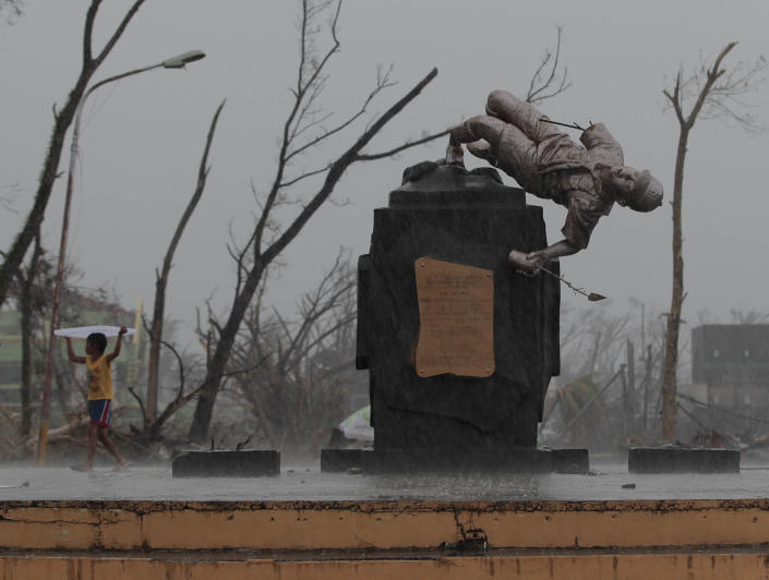 <p> A young survivor uses a plastic cover to protect him from rain as he passes by a damaged Boy Scout statue at typhoon ravaged Tacloban city, Leyte province, central Philippines on Tuesday, Nov. 12, 2013. Typhoon Haiyan, one of the strongest storms on record, slammed into six central Philippine islands on Friday leaving a wide swath of destruction. (AP Photo/Aaron Favila)</p>