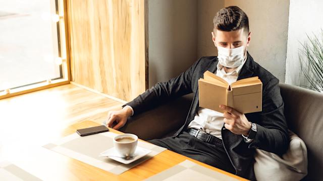 Handsome adult bearded man indoors in cafe. Lifestyle concept photo with copy space. Picture with book and protective face mask