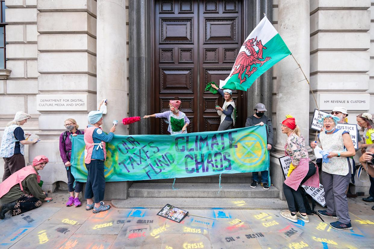 Activists from Extinction Rebellion dressed as cleaners hold a protest outside the offices of HM Revenue and Customs (HMRC) in Whitehall, Westminster, central London. Picture date: Tuesday August 24, 2021.