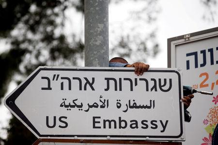 FILE PHOTO: A worker hangs a road sign directing to the U.S. embassy, in the area of the U.S. consulate in Jerusalem