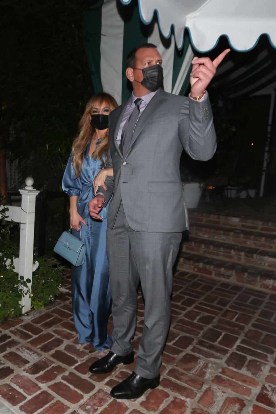 """<p>The singer wore a blue, sapphire-hued jumpsuit teamed with a matching-coloured Versace bag for her date night with fiancé Alex Rodriguez at San Vicente Bungalows in LA.</p><p>Earlier in the day, J-Lo's hair stylist, Chris Appleton, <a href=""""https://www.instagram.com/p/CGTNeWyhe93/?utm_source=ig_embed"""" rel=""""nofollow noopener"""" target=""""_blank"""" data-ylk=""""slk:announced"""" class=""""link rapid-noclick-resp"""">announced</a> on his Instagram account that the singer had got a new fringe ahead of her romantic night out.<br></p>"""