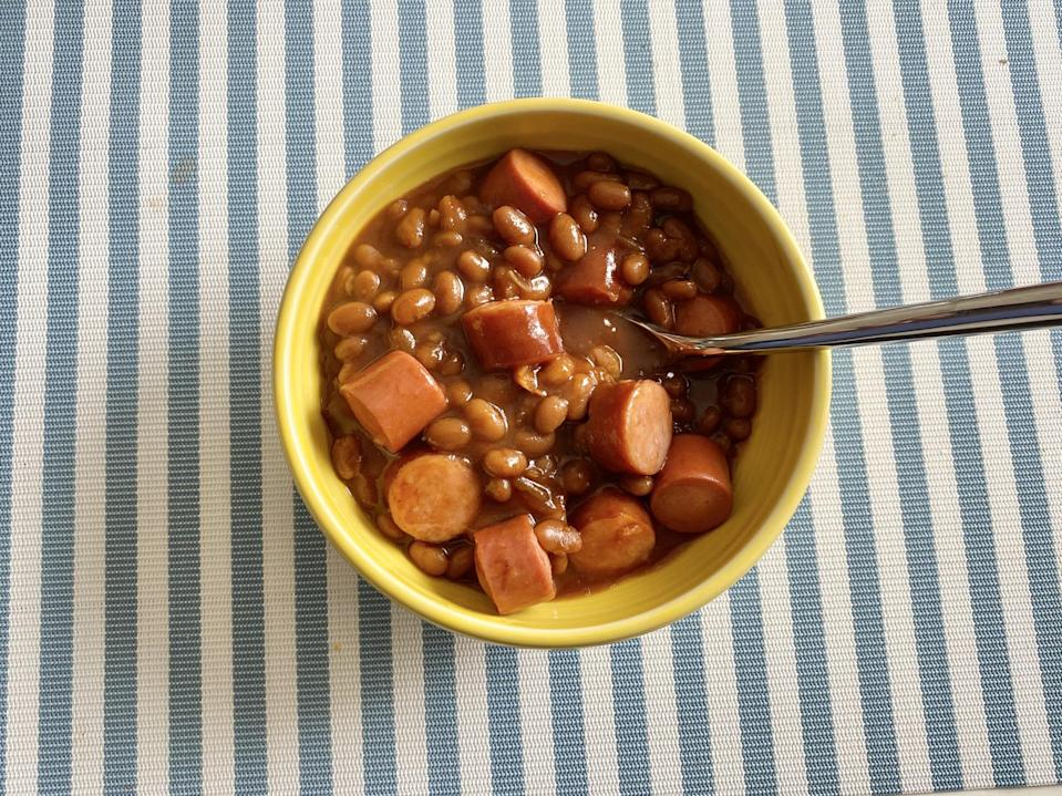 A bowl of baked beans with sliced hotdogs.