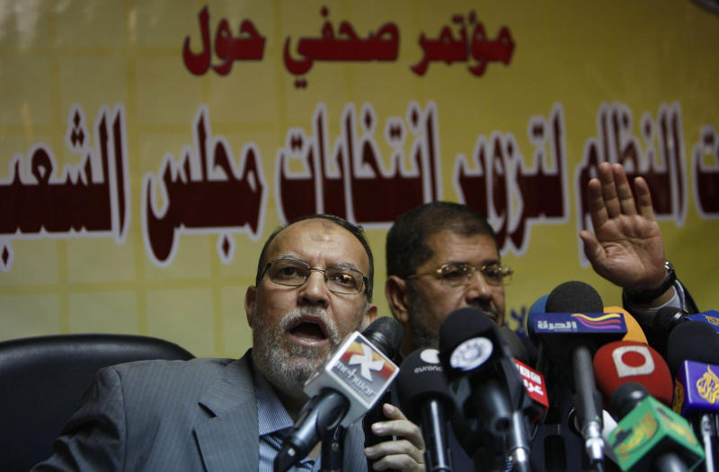 "Member of the guidance council of Egyptian biggest opposition group, the Muslim Brotherhood, Essam el-Erian, left and its spokesman Mohammed Morsi attend a press conference alleging early fraud in Egypt parliamentary elections, at the group's offices in Cairo, Egypt Monday, Nov. 22, 2010. The widespread crackdown on the opposition Muslim Brotherhood as it attempts to campaign for upcoming parliamentary polls means there will be ""no election"" in Egypt, said one of the group's lawmakers on Monday. Arabic in the background reads"" The government's excesses to forge the parliamentary elections"" . (AP Photo/Nasser Nasser)"