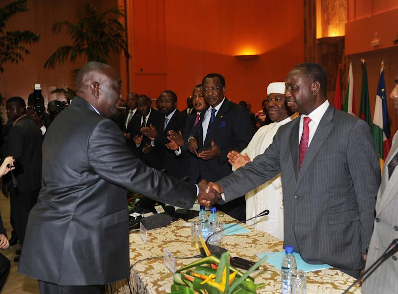 Central African Republic President Francois Bozize, right, shakes hands with Michel Djotodia, leader of the Seleka rebel alliance, as heads of state and other participants applaud, during peace talks in Libreville, Gabon, Friday, Jan. 11, 2013. Officials say that the rebel group controlling much of the northern half of the country have agreed to enter into a coalition with the government. The deal will allow President Francois Bozize to stay in office until his current term expires in 2016. (AP Photo/Joel Bouopda Tatou)