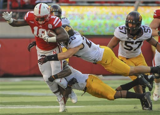 Minnesota's Troy Stoudermire, bottom, and Mike Rallis (26) tackle Nebraska's Quincy Enunwa (18) in the first half of an NCAA college football game in Lincoln, Neb., Saturday, Nov. 17, 2012. At right is Minnesota's Aaron Hill. (AP Photo/Dave Weaver)