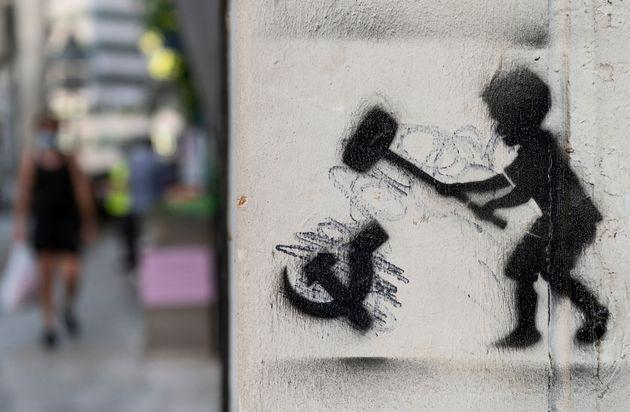 HONG KONG, CHINA - 2020/08/05: A graffiti is seen depicting a child hammering the communism symbol in Hong Kong. (Photo by Miguel Candela/SOPA Images/LightRocket via Getty Images) (Photo: SOPA Images via Getty Images)