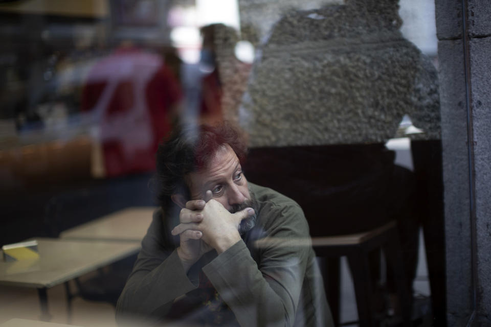 A man looks though a window inside of a coffee bar in downtown Madrid, Spain, Friday, Oct. 9, 2020. Spanish Prime Minister Pedro Sánchez is holding a Cabinet meeting to consider declaring a state of emergency for Madrid in order to impose stronger anti-virus restrictions on reluctant regional authorities. (AP Photo/Manu Fernandez)