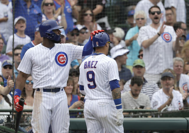 Chicago Cubs' Jason Heyward, left, pats Javier Baez on the helmet after Baez scored on a pinch-hit single by Tommy La Stella during the seventh inning of a baseball game against the Los Angeles Dodgers Wednesday, June 20, 2018, in Chicago. (AP Photo/Charles Rex Arbogast)