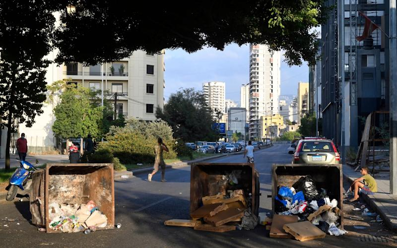 Anti-government protesters block a road with waste containers during a protest to demand a change of the sectarian system and finding solutions to the daily-living and economic crisis - WAEL HAMZEH/EPA-EFE/Shutterstock /Shutterstock