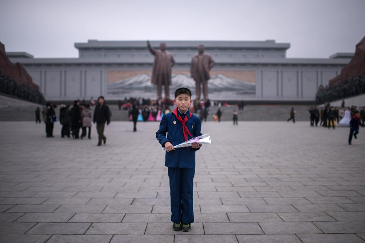 Kim Su-Min, 11, poses for a portrait before offering flowers to the statues of late North Korean leaders Kim Il-Sung and Kim Jong-Il at Mansudae hill in Pyongyang.
