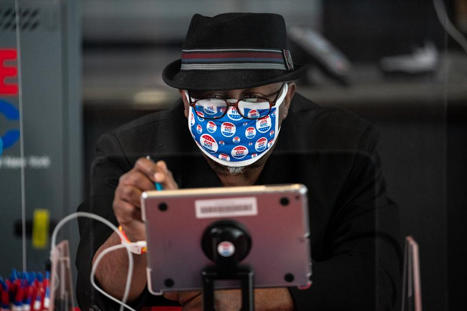 An election official wearing a protective mask at an early voting polling location in the Brooklyn borough of New York, U.S., on Monday, Oct. 26, 2020. (Photographer: Jeenah Moon/Bloomberg)
