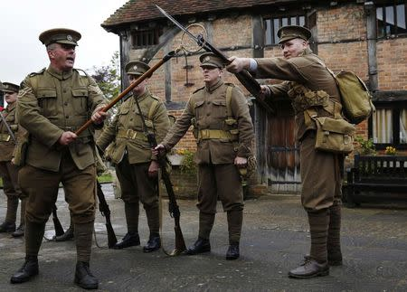 Factory landlord Lawrence Taylor (L), portraying a Colour Sergeant from the King's Royal Rifle Corps, part of the Rifles Living History Society, performs a drill with Connor Young (R) of the Queen's Own Royal West Kent Regiment Living History Group as they recreate the life of a First World War soldier at the Eden Valley Museum in Edenbridge in southeast England May 10, 2014. REUTERS/Luke MacGregor