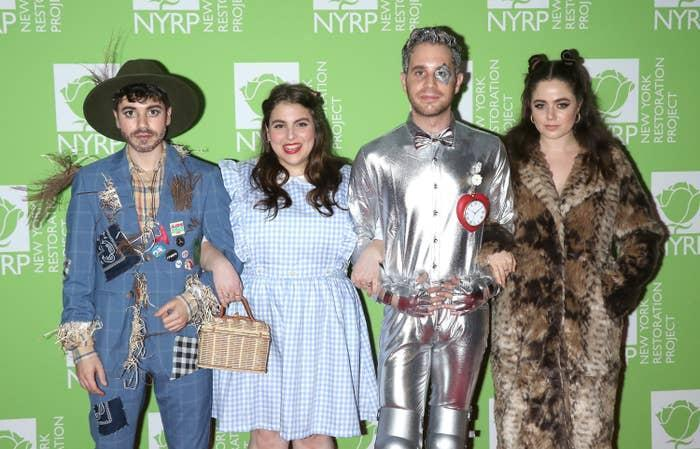 The couple and Beanie Feldstein posing in The Wizard of Oz Halloween costumes on a red carpet
