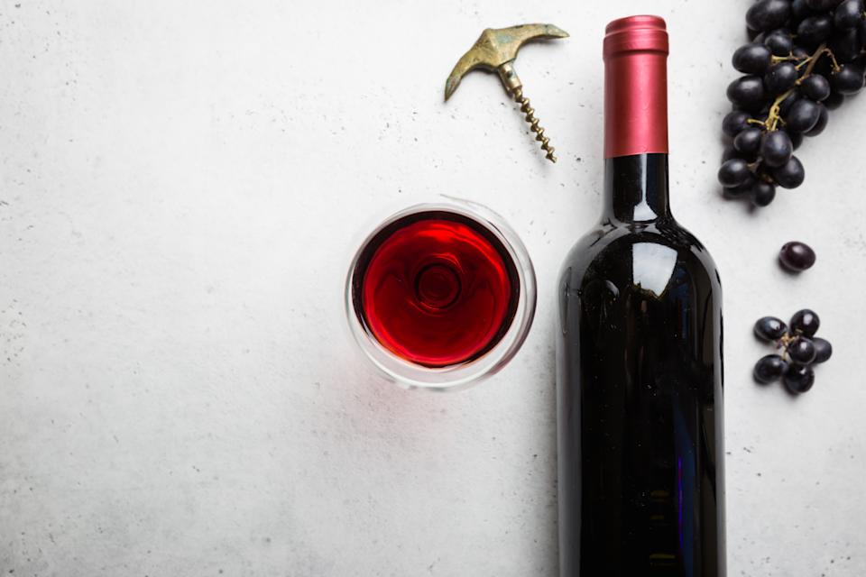 Red wine in a glass and ripe grapes on white background, top view