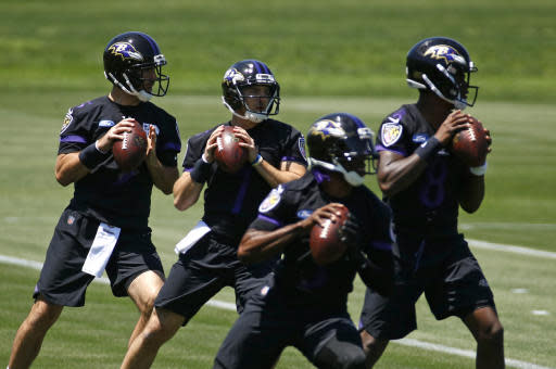 Baltimore Ravens quarterback Joe Flacco, left, runs a drill alongside fellow quarterbacks Josh Woodrum, second from left, Robert Griffin III and Lamar Jackson during an NFL football organized team activity at the team's headquarters in Owings Mills, Md., Thursday, May 24, 2018. (AP Photo/Patrick Semansky)