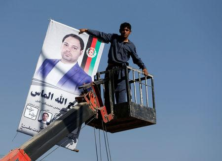 An Afghan man prepares a poster of a parliamentary election candidate ahead of the elections in Kabul, Afghanistan October 18, 2018. REUTERS/Omar Sobhani