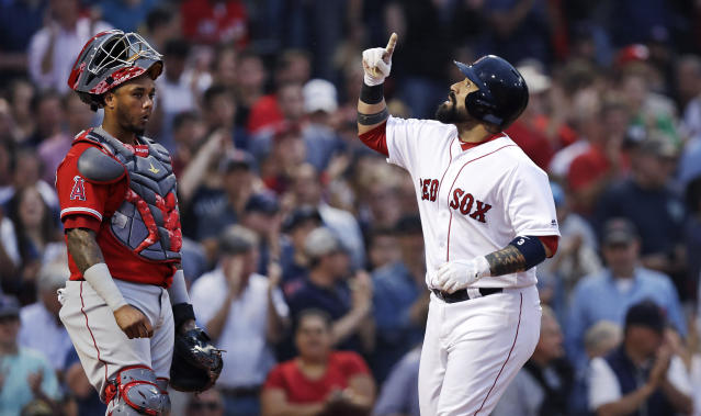 Boston Red Sox's Sandy Leon, right, points upward as he crosses home plate on a two-run home run off Los Angeles Angels starting pitcher Andrew Heaney during the second inning of a baseball game at Fenway Park in Boston, Wednesday, June 27, 2018. At left is Angels catcher Martin Maldonado. (AP Photo/Charles Krupa)