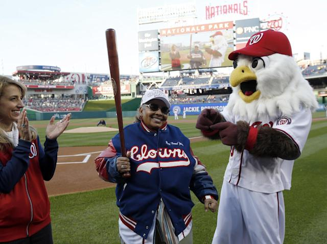 "Mamie ""Peanut"" Johnson, center, holds a bat she was presented as she is honored on before a baseball game between the Washington Nationals and the St. Louis Cardinals at Nationals Park Thursday, April 17, 2014, in Washington. Johnson was one of three women to play in the Negro Leagues. (AP Photo/Alex Brandon)"