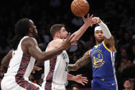 Golden State Warriors guard D'Angelo Russell (0) passes the ball past Brooklyn Nets forwards Joe Harris (12) and Taurean Prince, left, during the first half of an NBA basketball game Wednesday, Feb. 5, 2020, in New York. (AP Photo/Kathy Willens)