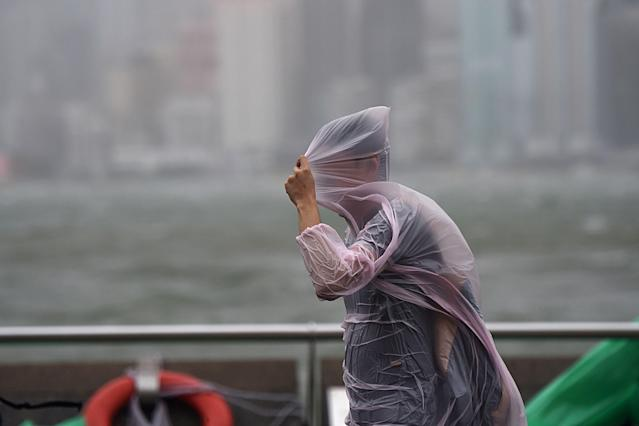 <p>A man shields himself with his plastic poncho during heavy winds and rain brought on by Typhoon Hato in Hong Kong on Aug. 23, 2017. (Photo: Anthony Wallace/AFP/Getty Images) </p>