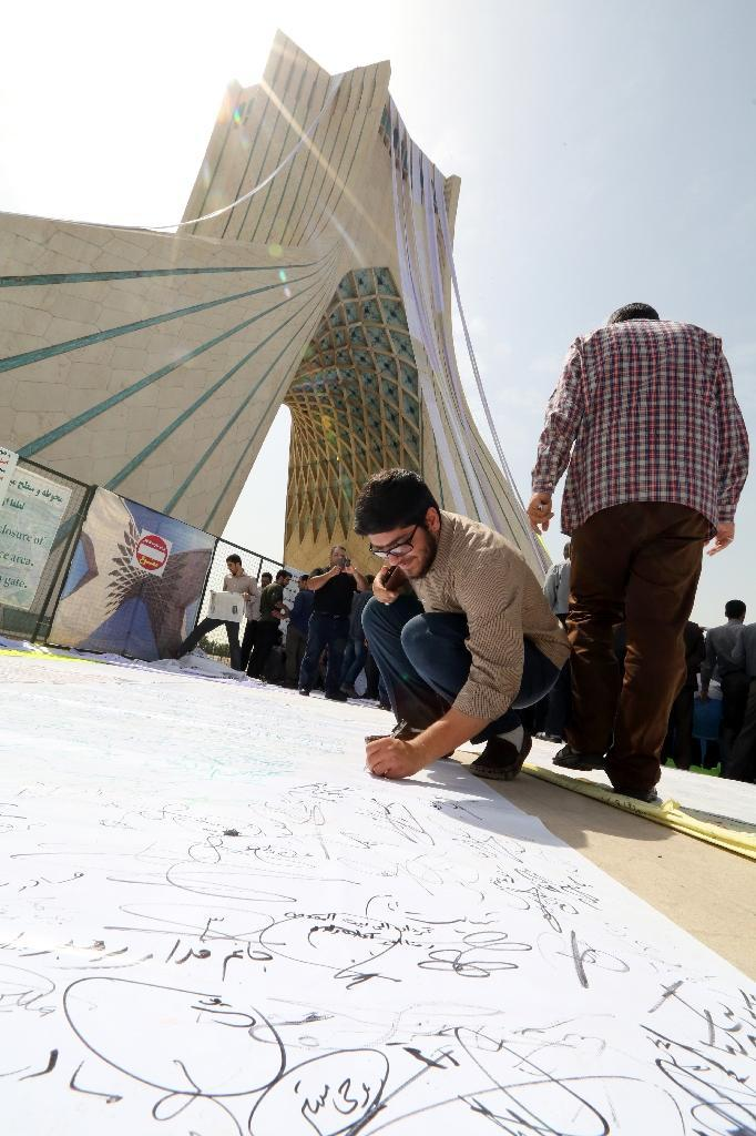 """A man signs a petition at Tehran's Azadi (Freedom) Square on June 30, 2015, calling for a """"good"""" nuclear deal (AFP Photo/Atta Kenare)"""