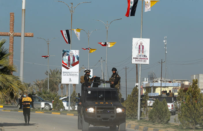 FILE - Iraqi security forces pass by Iraq and the Vatican flags and posters announcing visit of the Pope Francis in a street in Qaraqosh, Iraq, Monday, Feb. 22, 2021. Iraq was estimated to have more than 1 million Christians before the 2003 U.S.-led invasion that toppled dictator Saddam Hussein. Now, church officials estimate only few hundred remain within Iraq borders. The rest are scattered across the globe, resettling in far-flung places like Australia, Canada and Sweden as well as neighboring countries. (AP Photo/Hadi Mizban, File)
