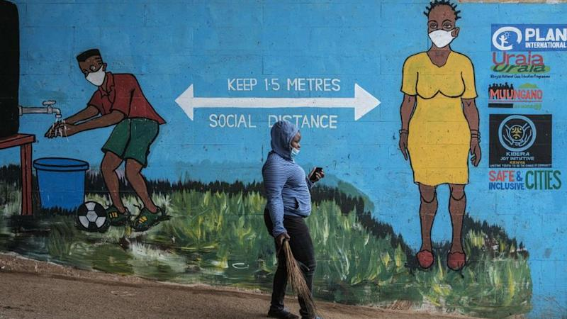 A woman with a face mask walks past graffiti that promotes social distancing, to curb the spread of the COVID-19 coronavirus, in Kibera, Nairobi, on July 15, 2020.