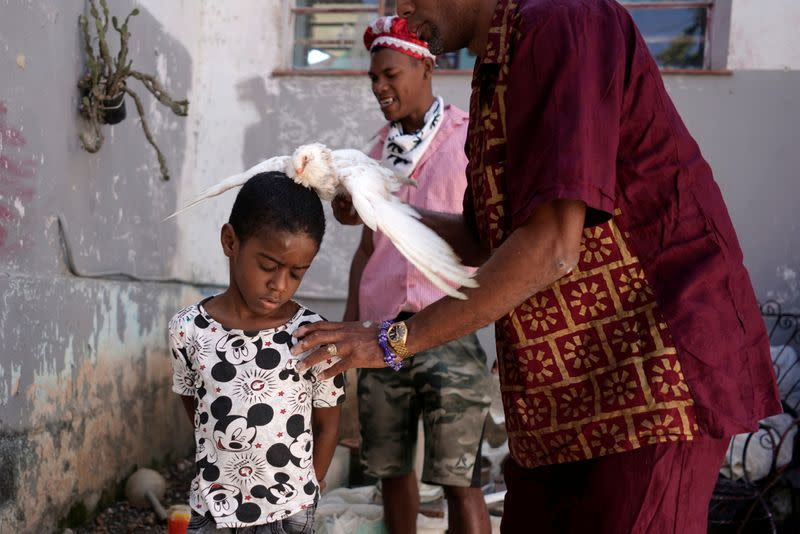 Jose Zamora, 8,  has a dove rubbed over his body during the Afro-Cuban religion Santeria ceremony amid concerns about the spread of the coronavirus disease outbreak, in Havana