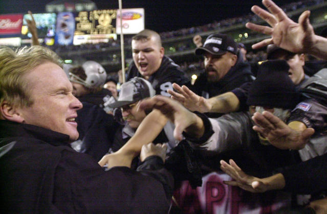 """FILE - In this Jan. 12, 2002, file photo, Oakland Raiders head coach Jon Gruden greets fans in the """"Black Hole"""" after the Raiders beat the New York Jets 38-24 during the AFC Wildcard playoff NFL football game in Oakland, Calif. The Raiders' final scheduled game in Oakland on Sunday, Dec. 15, 2019, will be an emotional one for players and coaches, as well as fans. (AP Photo/Paul Sakuma, File)"""