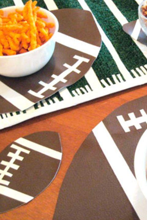 "<p>These placemats are the perfect accompaniment for your felt table runner! They're also super-durable, so there's no reason you can't keep using them after the big day. </p><p><em><a href=""http://www.chicaandjo.com/2010/01/21/football-shaped-table-mats-for-your-super-bowl-party/"" rel=""nofollow noopener"" target=""_blank"" data-ylk=""slk:Get the tutorial at Chica and Jo »"" class=""link rapid-noclick-resp"">Get the tutorial at Chica and Jo »</a></em> </p>"