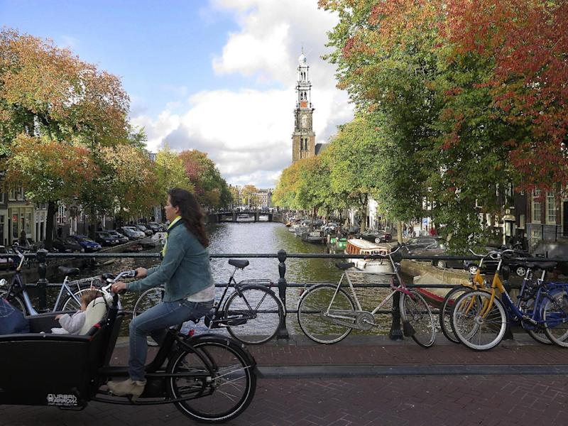 FILE - In this Oct. 17, 2014, file photo, a woman rides her bicycle across a bridge over Prinsengracht canal in front of autumnally colored trees in the center of Amsterdam. A Massachusetts Institute of Technology project called Treepedia, that maps trees in the world's major cities, is making it easier to determine where more green is needed. Trees play a critical role in urban environments, helping keep cities cool, mitigating air and noise pollution and just making them more pleasant places to live and work. (AP Photo/Margriet Faber, File)