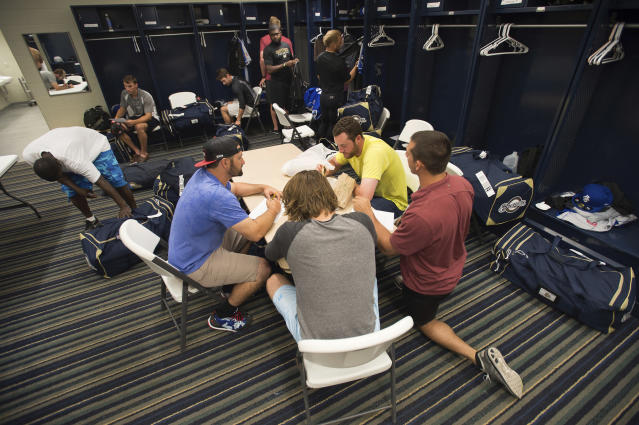 FILE - In this April 8, 2015, file photo, members of the Biloxi Shuckers minor league baseball team eat lunch before practice at the Pensacola Blue Wahoos' stadium in Pensacola, Fla. Major League Baseball is raising the minimum salary for minor league players in 2021, according to a memo sent from the commissioner's office to all 30 teams obtained by The Associated Press. (AP Photo/Michael Spooneybarger, File)
