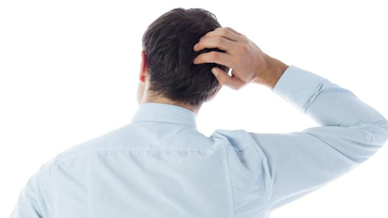 Businessman scratching his head on white background