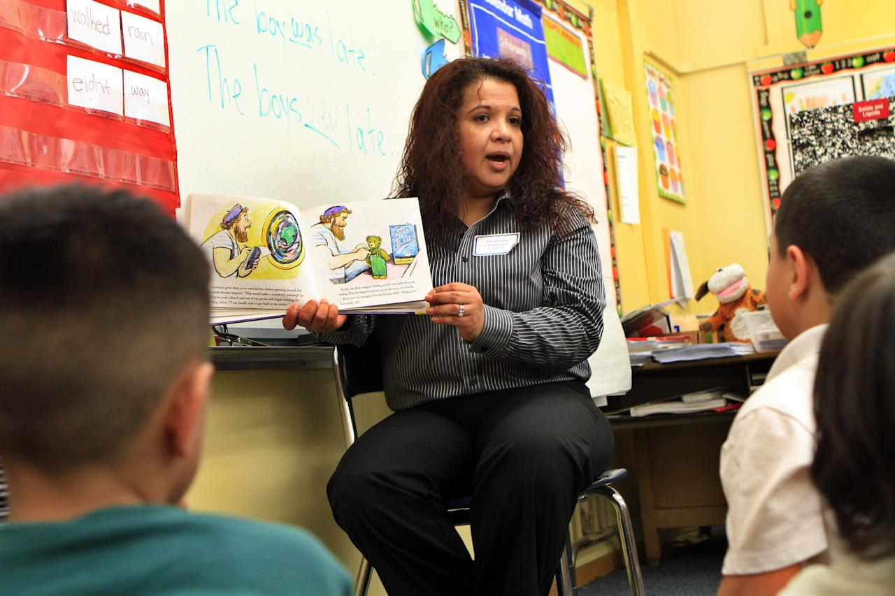 Teacher Martha Cedeno reads a story to her first grade class at Miramonte Elementary School in Los Angeles after the campus re-opened with all-new slate of teachers and administrators on Thursday, Feb. 9, 2012. The campus was closed for two days by Los Angeles Unified School District to replace the staff after two teachers where charged with lewd acts on students. (AP Photo/Los Angeles Times, Ifran Khan, Pool)