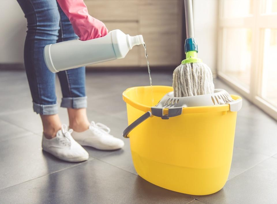 woman pouring cleaning chemicals in mop bucket