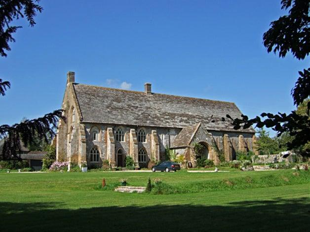 Most of Cerne Abbas's medieval monastery no longer exists. The major surviving building – a tithe barn, constructed in the 14th century – is now a houseWikiCommons
