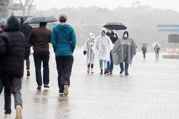 Football fans are seen arriving at ANZ Stadium in the rain in Sydney, Australia.