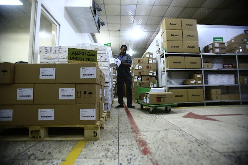 A worker unloads boxes of medecines at a governmental warehouse on November 27, 2016 in Khartoum from the UN Development Programme, but they could be more expensive than expected after cuts in fuel subsidies has lead to rising prices of other goods (AFP Photo/Ashraf Shazly)