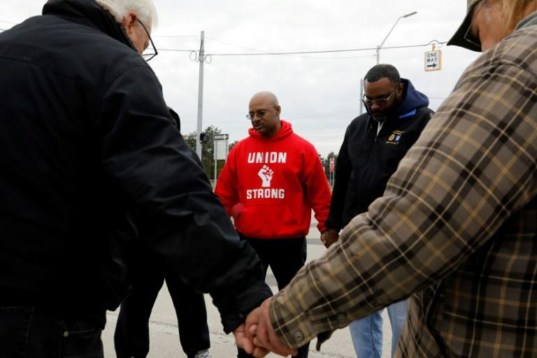 United Auto Workers (UAW) member Joe Ryan (C) leads a prayer circle to recite a strike closing prayer last month as General Motors workers voted to ratify a new contract (AFP Photo/JEFF KOWALSKY)