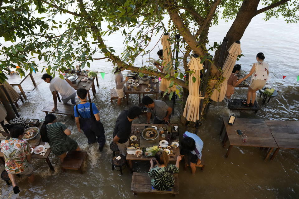 """Customers of the riverside Chaopraya Antique Café react to a boat's wake as they enjoy themselves in the extraordinary high water levels in the Chao Phraya River in Nonthaburi, near Bangkok, Thailand, Thursday, Oct. 7, 2021. The flood-hit restaurant has become an unlikely dining hotspot after fun-loving foodies began flocking to its water-logged deck to eat amid the lapping tide. Now, instead of empty chairs and vacant tables, the cafe is as full as ever, offering an experience the canny owner has re-branded as """"hot-pot surfing."""" (AP Photo/Sakchai Lalit)"""