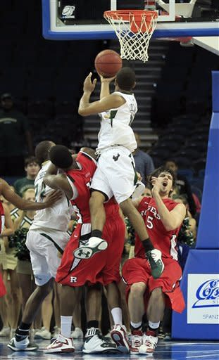South Florida guard Anthony Collins (11) goes up for what proved to be the game-winning basket over the Rutgers defense, including forward Gilvydas Biruta (55), during the second half of an NCAA college basketball game Sunday Jan. 1, 2012, in Tampa, Fla. South Florida won 67-65. (AP Photo/Chris O'Meara)