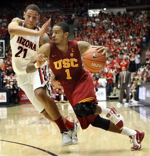 Southern California's Jio Fontan (1) drives into the lane around Arizona's Brandon Ashley (21) during the first half of an NCAA college basketball game at McKale Center in Tucson, Ariz., Saturday, Jan. 26, 2013. (AP Photo/Wily Low)