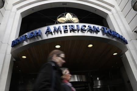 People walk past the British American Tobacco offices in London
