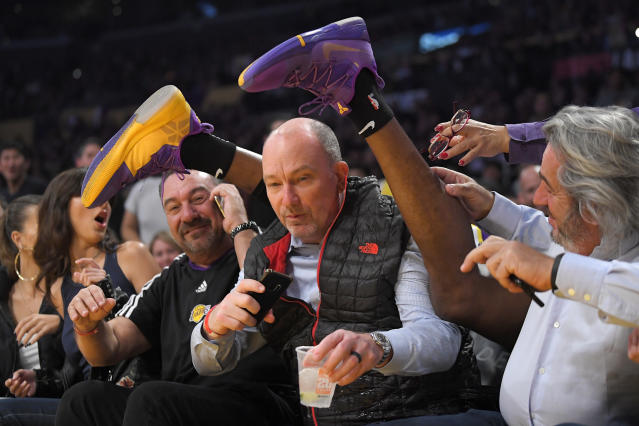 Los Angeles Lakers center Dwight Howard's feet are seen after he crashed into the seating are while chasing a loose ball during the first half of the team's NBA basketball game against the Orlando Magic on Wednesday, Jan. 15, 2020, in Los Angeles. (AP Photo/Mark J. Terrill)