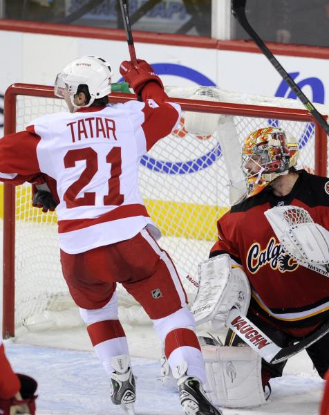 Detroit Red Wings' Tomas Tartar, left, from Slovakia, celebrates Justin Abdelkader's goal against Calgary Flames goalie Joey MacDonald during the third period of an NHL hockey game in Calgary, Alberta, Friday, Nov. 1, 2013. (AP Photo/The Canadian Press, Larry MacDougal)